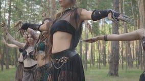 Bailarines hábiles de las mujeres con maquillaje y en los trajes fabulosos místicos que bailan danza maravillosa en naturaleza Ha almacen de video