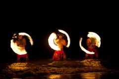 Bailarines hawaianos del fuego en el océano Imagen de archivo
