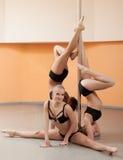 Bailarines jovenes lindos del polo que presentan con el pilón Fotos de archivo