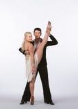 Bailarines latinos del salón de baile con el vestido grisáceo - elevación de la pierna Fotos de archivo libres de regalías