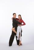 Bailarines latinos del salón de baile con el vestido negro y rojo - pierna levantada Foto de archivo libre de regalías