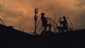 Bailarines muchacha y baile del gay en la puesta del sol del tejado almacen de video