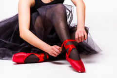 Bailarín de ballet que ata los deslizadores rojos alrededor de su tobillo Fotos de archivo libres de regalías