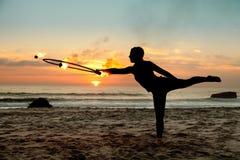Bailarín del fuego contra puesta del sol Fotos de archivo