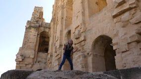 Baile adorable de la muchacha y salto en alta piedra en el fondo de la fortaleza Amphitheatre del EL Jem metrajes