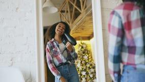 Baile afroamericano divertido rizado de la muchacha y canto con el secador de pelo delante del espejo en casa almacen de video