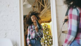 Baile afroamericano divertido rizado de la muchacha y canto con el secador de pelo delante del espejo en casa Fotografía de archivo libre de regalías
