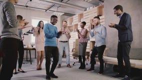 Baile afroamericano feliz del empleado con los colegas en las fiestas en la oficina, celebrando la cámara lenta del logro del neg almacen de metraje de vídeo