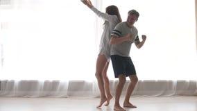 Baile alegre de la pareja de matrimonios en sus pijamas por la ventana por la mañana almacen de video