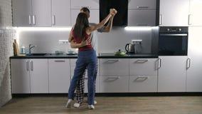 Baile alegre de los pares en pijamas en cocina almacen de metraje de vídeo