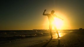Baile alegre del hombre en la playa Él salta en el sol El hombre se está divirtiendo Él es feliz Silueta de un hombre en