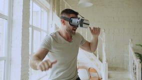 Baile alegre del hombre joven mientras que consigue experiencia usando 360 vidrios de las auriculares de VR de realidad virtual e metrajes