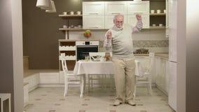 Baile alegre del viejo hombre en la cocina almacen de video