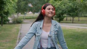 Baile alegre hermoso de la muchacha que camina en el parque con los auriculares almacen de video