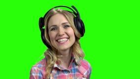 Baile alegre joven de la mujer con los auriculares almacen de metraje de vídeo
