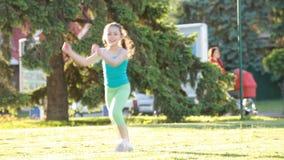 Baile alegre y feliz de la niña y el jugar en hierba verde en el parque almacen de metraje de vídeo
