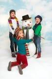 Baile alrededor del muñeco de nieve Imágenes de archivo libres de regalías