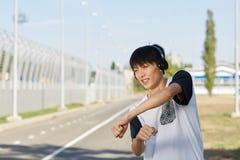Baile asiático adolescente del muchacho en auriculares en un fondo de la calle Años adolescentes de concepto Copie el espacio Fotografía de archivo libre de regalías
