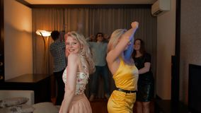 Baile atractivo atractivo de dos muchachas en el partido con los amigos detrás almacen de metraje de vídeo