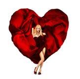 Baile atractivo de la mujer joven con el corazón de seda de la tarjeta del día de San Valentín Fotografía de archivo