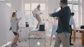 Baile caucásico feliz joven así como con colegas, cámara lenta del jefe de la compañía de la celebración del éxito del equ almacen de metraje de vídeo