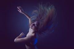 Baile caucásico moreno joven de la mujer y su pelo que atraviesan el aire Foto de archivo