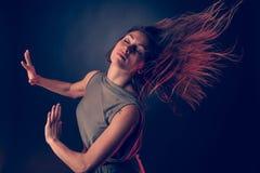 Baile caucásico moreno joven de la mujer y su pelo que atraviesan el aire Fotografía de archivo