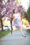 Baile de la chica joven y salto debajo de los ?rboles florecientes de Sakura fotos de archivo