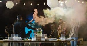 Baile de la gente con humo coloreado en un tejado almacen de metraje de vídeo