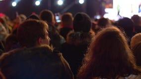 Baile de la juventud en una muchedumbre de gente en el fondo de la escena retroiluminada en un concierto de la calle por la tarde almacen de video