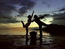 Baile de la mama y de la hija en la puesta del sol Imagen de archivo