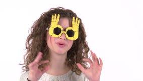 Baile de la muchacha del niño en vidrios divertidos Fondo blanco almacen de video