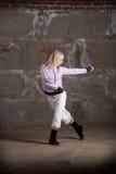 Baile de la muchacha del salto de la cadera sobre el ladrillo gris wal Fotos de archivo