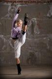 Baile de la muchacha del salto de la cadera sobre el ladrillo gris wal Imagen de archivo