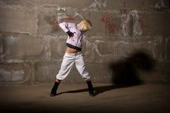 Baile de la muchacha del salto de la cadera sobre el ladrillo gris wal Fotos de archivo libres de regalías