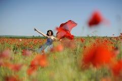 Baile de la muchacha en amapolas con el paño del rojo del vuelo Imágenes de archivo libres de regalías