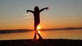 Baile de la muchacha en la playa por la tarde en la puesta del sol metrajes