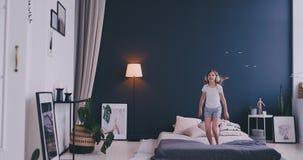 Baile de la muchacha de Litl en cama y el escuchar la música con los auriculares inalámbricos Tiempo libre y concepto moderno de  almacen de metraje de vídeo