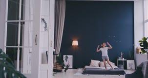 Baile de la muchacha de Litl en cama y el escuchar la m?sica con los auriculares inal?mbricos Tiempo libre y concepto moderno de  metrajes