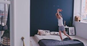 Baile de la muchacha de Litl en cama y el escuchar la m?sica con los auriculares inal?mbricos Tiempo libre y concepto moderno de  almacen de video