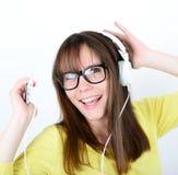 Baile de la mujer con los auriculares de botón/los auriculares que escuchan la música en la P.M. Fotografía de archivo