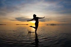 baile de la mujer en el mar bajo en la salida del sol Fotos de archivo