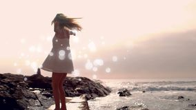 Baile de la mujer joven en la orilla del agua en la playa con efecto luminoso