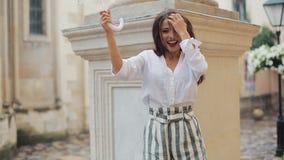 Baile de la mujer joven y diversión hermosos el tener con el paraguas en la calle de la ciudad vieja después de lluvia metrajes
