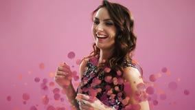 Baile de la mujer rodeado por efecto de las burbujas contra fondo rosado