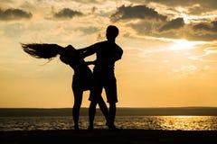 Baile de la silueta de los pares en la playa foto de archivo libre de regalías