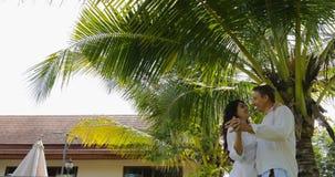 Baile de los pares debajo de la palmera en jardín tropical cerca de la casa del chalet, del hombre feliz y de amantes de la mujer almacen de metraje de vídeo