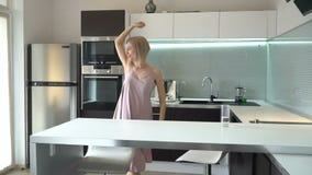 Baile de mediana edad alegre de la mujer en la cocina almacen de video