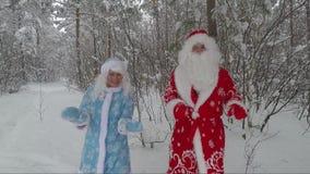 Baile de Santa Claus y de la nieta en el bosque del pino del invierno metrajes