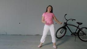 Baile del adolescente de la muchacha en un fondo gris Danza de la calle almacen de metraje de vídeo